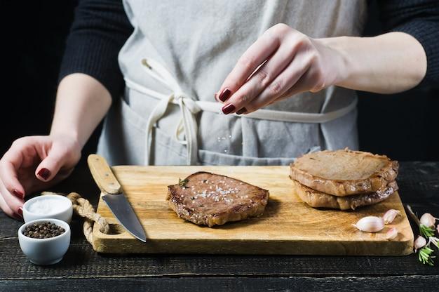 Entregue o bife salgado cozinheiro chefe em uma placa de desbastamento de madeira. Foto Premium