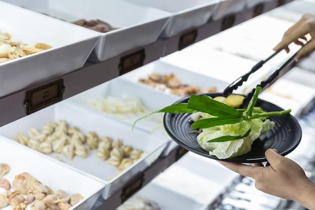 Entregue seleto e beliscando legumes frescos na placa preta. Foto Premium