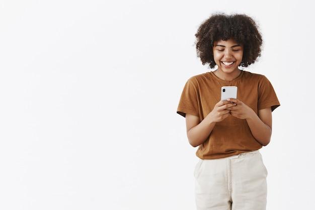 Entretido fofa feliz adolescente afro-americana com penteado afro em uma camiseta marrom segurando um smartphone e rindo de um vídeo engraçado na internet usando o dispositivo para se divertir Foto gratuita