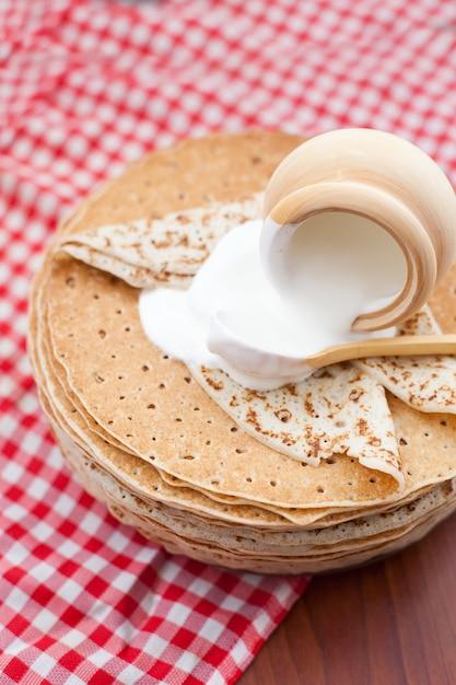 Entrudo, panquecas com creme de leite na parede de madeira. a vista do topo. o conceito de culinária, mardi gras Foto Premium
