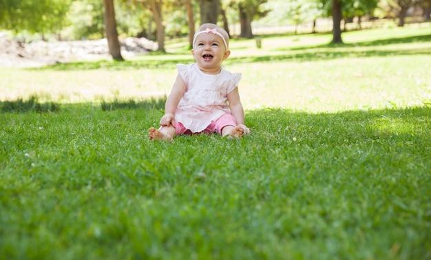 Entusiástico bebê fofo sentado na grama no parque | Foto Premium