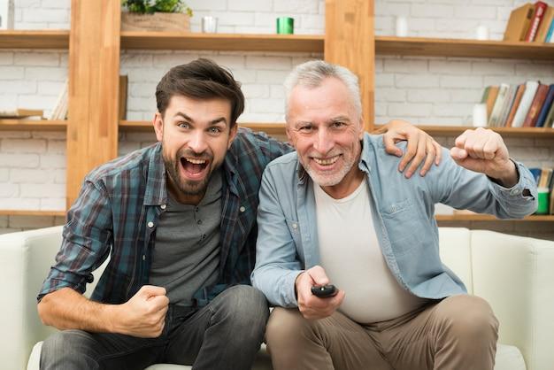 Envelhecido, homem feliz, com, controle remoto, e, jovem, chorando, sujeito, tv assistindo, ligado, sofá Foto gratuita