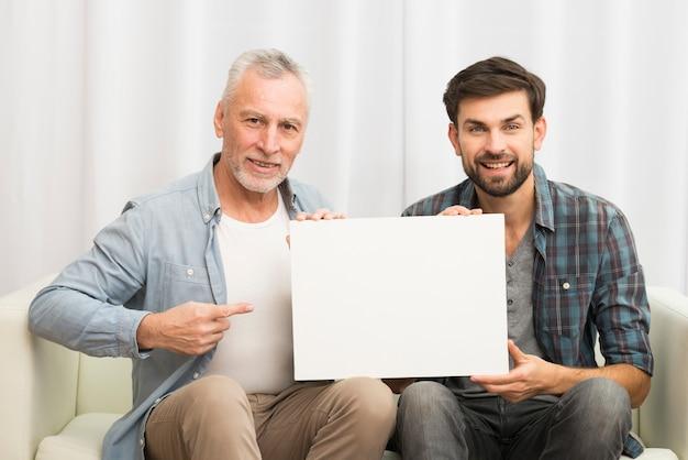 Envelhecido, homem sorridente, apontar, papel, e, jovem, feliz, sujeito, ligado, sofá Foto gratuita