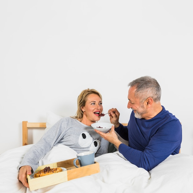Envelhecido, homem sorridente, dar, bagas, para, mulher, em, duvet, perto, café da manhã, ligado, bandeja, cama Foto gratuita