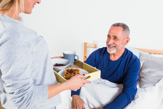 Envelhecido, mulher, dar, café manhã, para, sorrindo, homem, em, duvet, cama Foto gratuita