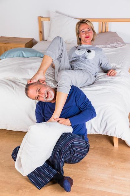 Envelhecido, mulher sorridente, com, pernas, ligado, homem, com, travesseiro, perto, cama Foto gratuita