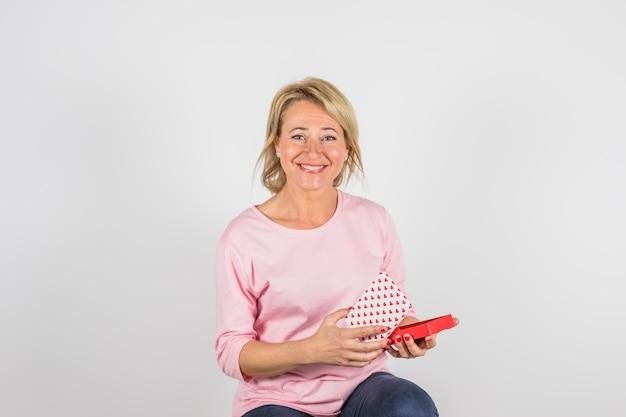 Envelhecido, mulher sorridente, em, rosa, blusa, com, caixa presente Foto gratuita