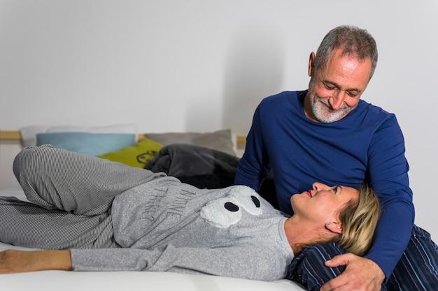 Envelhecido, mulher sorridente, mentindo, ligado, homem, pernas, cama Foto gratuita