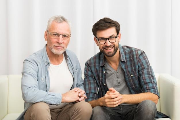 Envelhecido, sorrindo, homem, e, jovem, feliz, sujeito, clasping, mãos sofá Foto gratuita