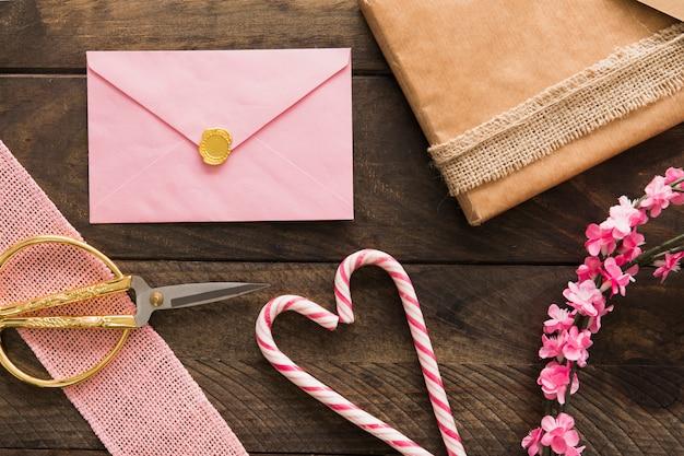 Envelope, bastões de doces, presentes e galhos com flores Foto gratuita