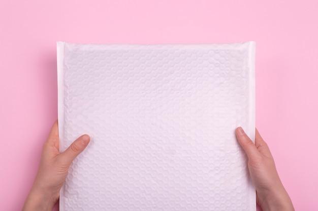 Envelope branco em branco com pacote postal nas mãos em um fundo rosa. indústria postal e entrega de cargas. Foto Premium