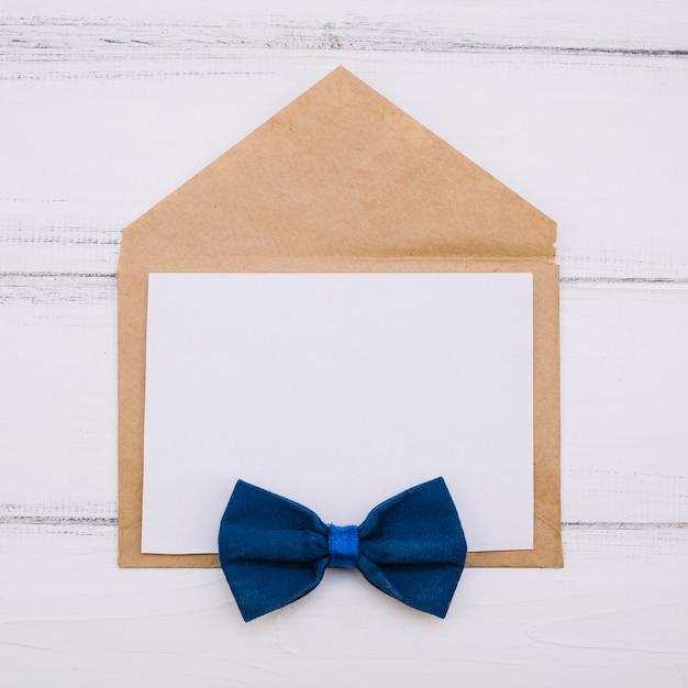 Envelope com papel e gravata borboleta Foto gratuita