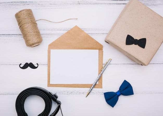 Envelope com papel perto da caixa, fios e pulseira de couro Foto gratuita