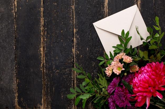 Envelope com um buquê de flores em uma madeira escura vintage Foto Premium