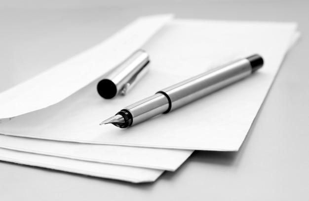 Envelope de correio e caneta em cima da mesa Foto Premium