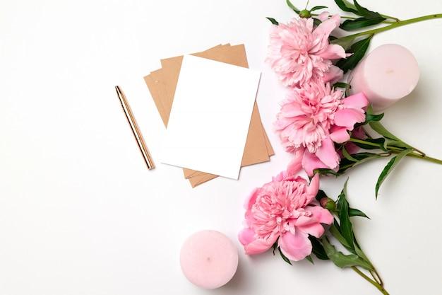 Envelope de ofício com uma folha de papel com um buquê de peônias rosa em cinza Foto Premium
