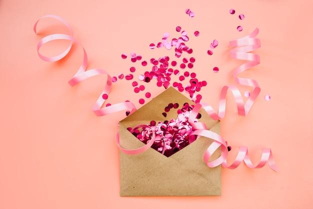 Envelope de papel com confete rosa e fitas Foto gratuita