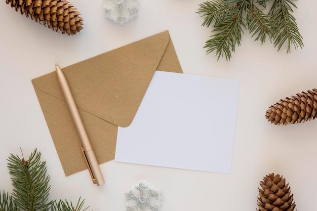 Envelope de papelaria e papel com cones de coníferas Foto gratuita