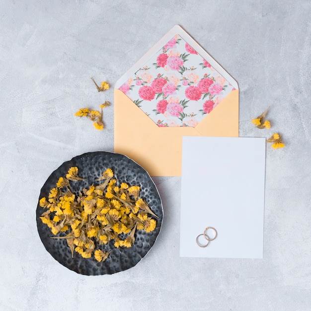 Envelope perto de papel branco e conjunto de flores secas Foto gratuita