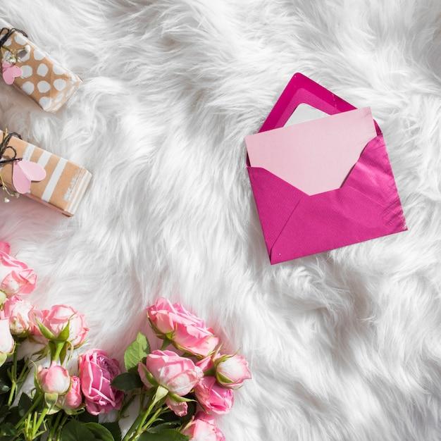 Envelope perto de presentes e flores frescas em colcha de lã Foto gratuita