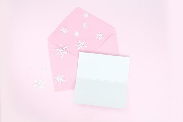 Envelope rosa aberto com flocos de neve de natal e folha de papel em branco Foto Premium