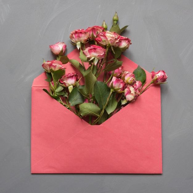 Envelope vermelho aberto com rosas rosa em cinza Foto Premium