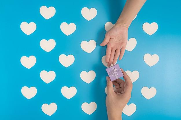 Enviando uma caixa de presente em azul com padrão de corações brancos Foto Premium