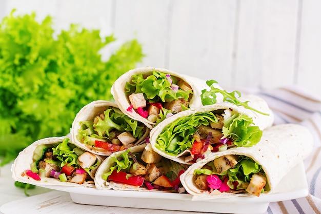 Envoltórios mexicanos da tortilha do fajita da comida da rua com a faixa grelhada da galinha e os legumes frescos. Foto Premium