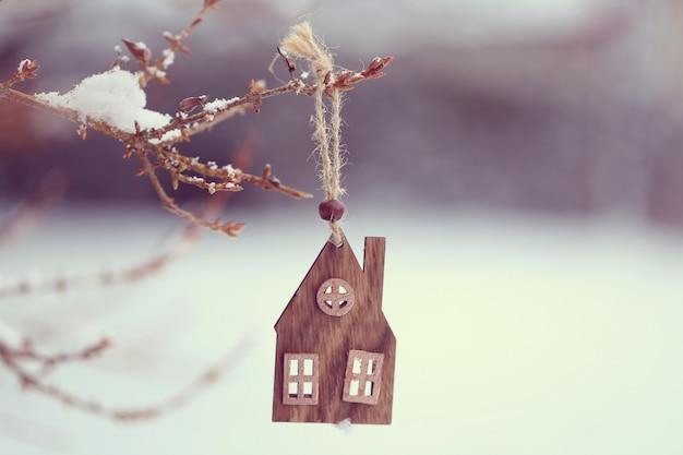Época de natal. casinha de madeira em um galho no inverno e neve Foto Premium