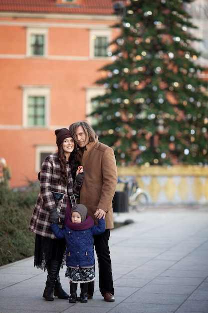 Época de natal. família feliz - mãe, pai e filha andando na cidade e se divertindo Foto Premium
