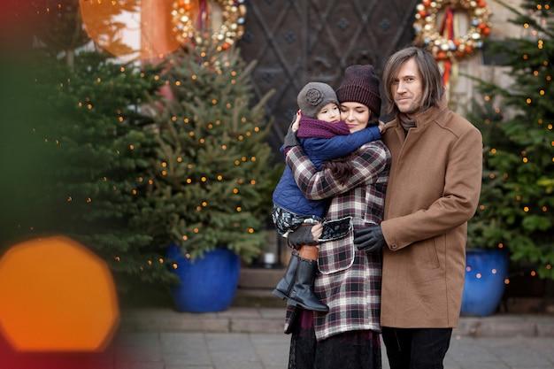 Época de natal. família feliz - mãe, pai e filha andando na cidade e se divertindo. Foto Premium