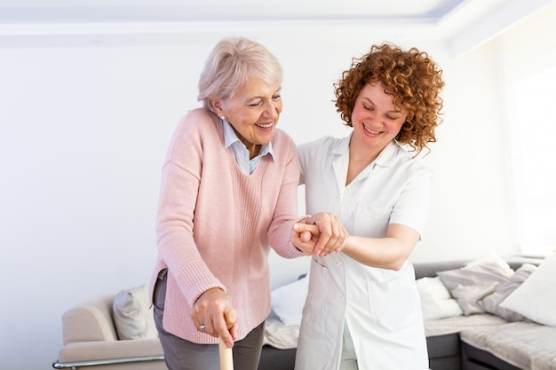 Equipa de tratamento nova que apoia a mulher deficiente superior com bengala. Foto Premium