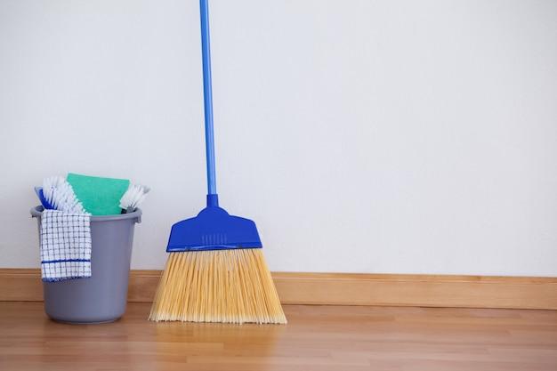 Equipamento de limpeza no piso de madeira contra a parede Foto Premium