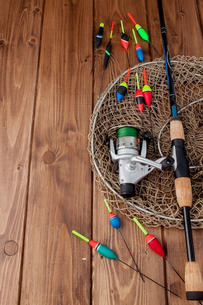 Equipamento de pesca - flutuador de pesca com vara de pescar e iscas em uma bela madeira azul Foto Premium