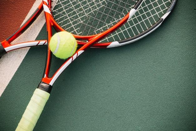 Equipamento de tênis com uma bola de tênis Foto gratuita