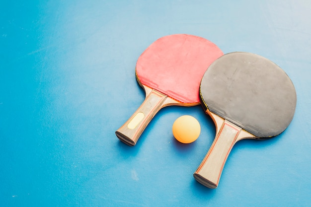Equipamento de ténis de mesa na mesa azul Foto gratuita