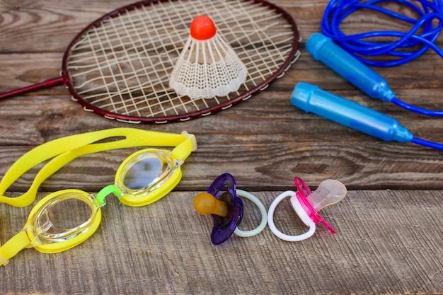 Equipamento desportivo: o passarinho está na raquete, pular corda, óculos de natação e tênis no fundo de madeira Foto Premium
