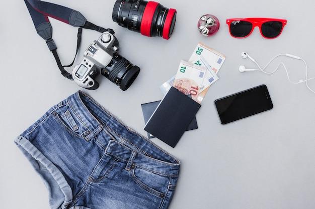 Equipamentos de viagem com roupas em fundo cinza Foto gratuita