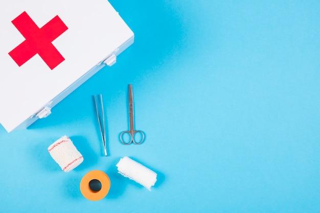 Equipamentos médicos com kit de primeiros socorros em fundo azul Foto gratuita