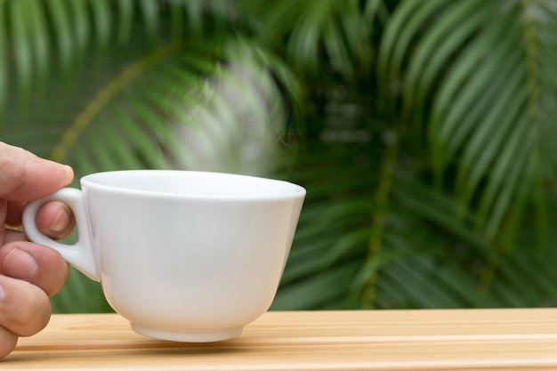 Equipe a mão que guarda uma caneca de café branco em uma tabela e em uma palmeira de madeira no fundo. Foto Premium