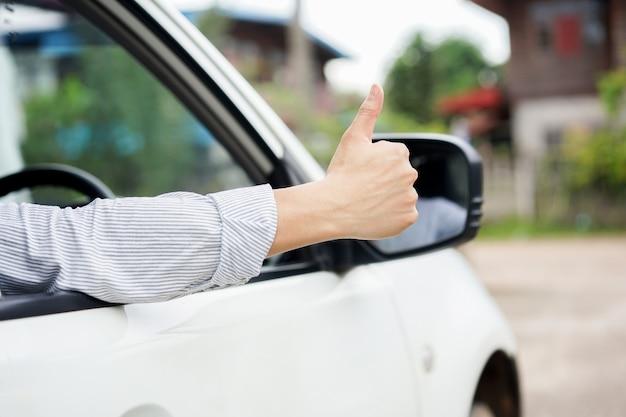 Equipe a mão que mostra o polegar acima através da janela de carro para a segurança do conceito de condução. Foto Premium