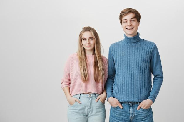 Equipe amigável, colaboração e cooperação. casal sorridente feliz, vestindo jeans e roupas de malha Foto gratuita