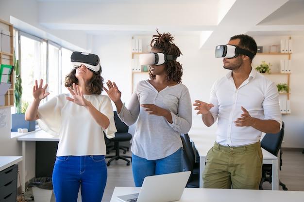 Equipe animada de três simuladores vr de teste Foto gratuita