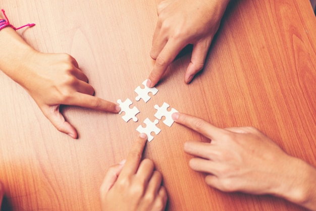 Equipe as mãos que conectam a parte do enigma dos pares no escritório. negócio, sucedido Foto Premium