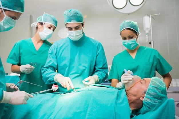 Equipe cirúrgica com uma barriga paciente Foto Premium
