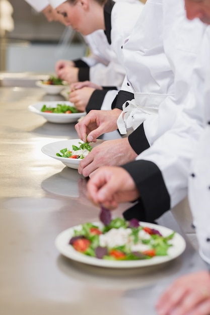 Equipe de cozinheiros garnishing saladas Foto Premium