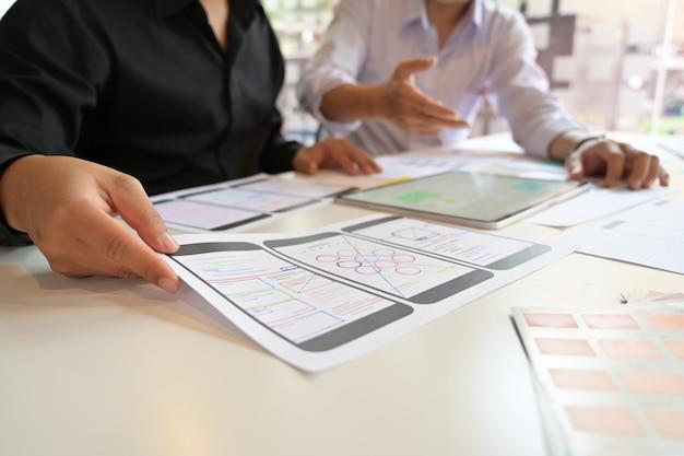 Equipe de designer ux usando o tablet projetando layout de telefone móvel web wireframe Foto Premium