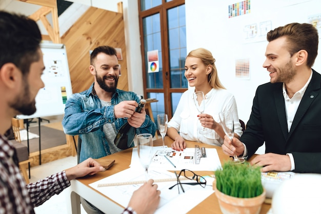 Equipe de designers arquitetos abrindo champanhe. Foto Premium