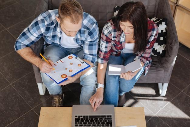 Equipe de designers. jovens criativos e simpáticos sentados juntos e olhando para a tela do laptop enquanto trabalham juntos em um projeto Foto Premium