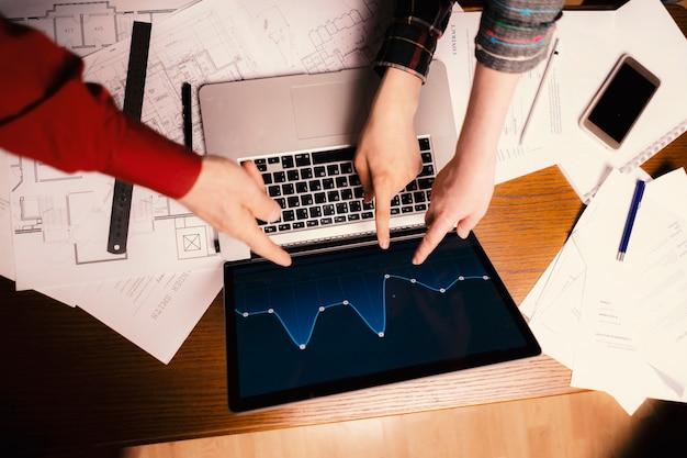 Equipe de empresários talentosos aponte no gráfico no laptop Foto Premium